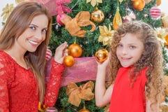 Ciérrese para arriba de la muchacha feliz que adorna el árbol de navidad con su mamá que sostiene las bolas de oro, concepto de l Imagen de archivo libre de regalías