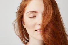 Ciérrese para arriba de la muchacha hermosa blanda joven con el pelo rojo que sonríe con los ojos cerrados sobre el fondo blanco Imagenes de archivo