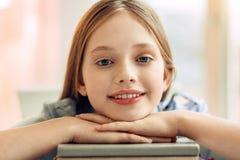 Ciérrese para arriba de la muchacha linda que presenta en la pila de libros Imagen de archivo