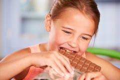 Ciérrese para arriba de la muchacha que come la barra del chocolate Fotos de archivo libres de regalías