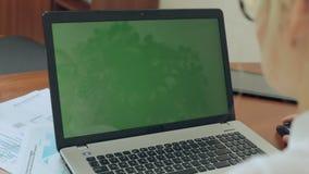 Ciérrese para arriba de la muchacha que trabaja en un ordenador portátil con verde almacen de metraje de vídeo