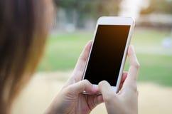 Ciérrese para arriba de la muchacha que usa el teléfono elegante Foto de archivo libre de regalías