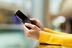Ciérrese para arriba de la muchacha que usa el teléfono elegante móvil Fotos de archivo