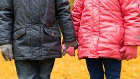 Ciérrese para arriba de la muchacha y del muchacho que llevan a cabo las manos al aire libre Imagenes de archivo