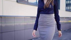 Ciérrese para arriba de la mujer atractiva vestida en la blusa azul, la falda gris y los zapatos de tacón alto caminando a lo lar metrajes