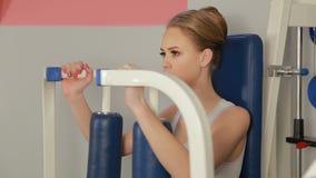 Ciérrese para arriba de la mujer caucásica rubia de la aptitud del gimnasio que hace ejercicios de brazos en una máquina metrajes