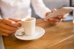 Ciérrese para arriba de la mujer de las manos que usa su teléfono celular en barra Fotos de archivo libres de regalías