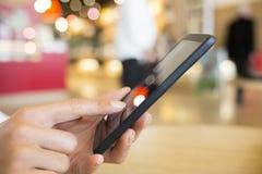 Ciérrese para arriba de la mujer de las manos que usa su teléfono celular en una estación de tren Imágenes de archivo libres de regalías