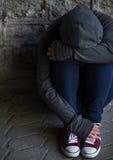 Ciérrese para arriba de la mujer del adicto que oculta su cara en la calle Foto de archivo