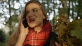 Ciérrese para arriba de la mujer del happyyoung que habla en el teléfono móvil en parque hermoso del otoño almacen de video