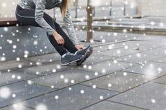 Ciérrese para arriba de la mujer deportiva que ata los zapatos al aire libre Foto de archivo
