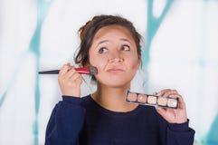 Ciérrese para arriba de la mujer hermosa joven que sostiene una paleta del componer y que hace maquillaje loco en su cara usando  Fotografía de archivo libre de regalías