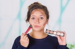 Ciérrese para arriba de la mujer hermosa joven que sostiene una paleta del componer y que hace maquillaje loco en su cara usando  Foto de archivo libre de regalías