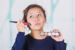 Ciérrese para arriba de la mujer hermosa joven que sostiene una paleta del componer y que hace maquillaje loco en su cara usando  Fotos de archivo libres de regalías