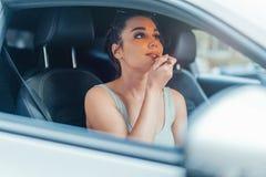 Ciérrese para arriba de la mujer hermosa que consigue sus labios pintados mientras que se sienta en coche foto de archivo libre de regalías
