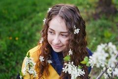 Ciérrese para arriba de la mujer joven hermosa que camina en un jardín floreciente de la primavera Fotos de archivo libres de regalías