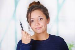 Ciérrese para arriba de la mujer joven hermosa que sostiene un lápiz de ojos en su mano, en un fondo borroso Imagen de archivo