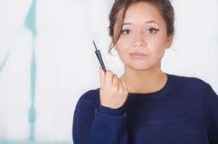 Ciérrese para arriba de la mujer joven hermosa que sostiene un lápiz de ojos en su mano, en un fondo borroso Imagen de archivo libre de regalías