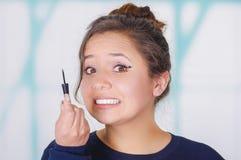 Ciérrese para arriba de la mujer joven preocupante que sostiene un lápiz de ojos y que hace maquillaje loco en su cara, en un fon Foto de archivo libre de regalías