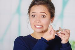 Ciérrese para arriba de la mujer joven preocupante que sostiene un lápiz de ojos y que hace maquillaje loco en su cara, en un fon Fotografía de archivo