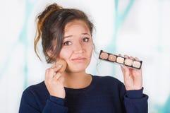 Ciérrese para arriba de la mujer joven preocupante que sostiene una paleta del componer y que hace maquillaje loco en su cara usa Imágenes de archivo libres de regalías