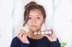 Ciérrese para arriba de la mujer joven preocupante que sostiene una paleta del componer y que hace maquillaje loco en su cara usa Imagenes de archivo