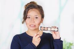 Ciérrese para arriba de la mujer joven preocupante que sostiene una paleta del componer y que hace maquillaje loco en su cara usa Fotos de archivo