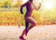 Ciérrese para arriba de la mujer joven que corre en parque del otoño Imágenes de archivo libres de regalías