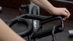 Ciérrese para arriba de la mujer joven, que está sosteniendo el manillar de la bicicleta inmóvil, cámara lenta almacen de metraje de vídeo