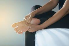 Ciérrese para arriba de la mujer de las manos que tiene un único dolor del pie, sensación femenina agotada y dolorosa imagen de archivo