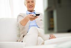 Ciérrese para arriba de la mujer mayor feliz que ve la TV en casa Fotos de archivo libres de regalías