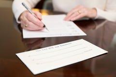 Ciérrese para arriba de la mujer mayor que firma por último y testamento en casa fotografía de archivo