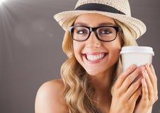 Ciérrese para arriba de la mujer milenaria que sonríe con café y señale por medio de luces contra fondo marrón Foto de archivo libre de regalías