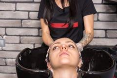Ciérrese para arriba de la mujer morena joven que tiene b lavado y jabonado del pelo imagen de archivo