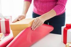 Ciérrese para arriba de la mujer que adorna regalos de Navidad Foto de archivo