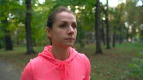 Ciérrese para arriba de la mujer que ata cordones y el funcionamiento de zapato a través de un parque del otoño en la puesta del  almacen de metraje de vídeo