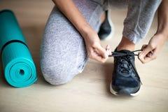 Ciérrese para arriba de la mujer que ata los cordones de zapatos de entrenamiento antes de ejercicio en casa imagenes de archivo
