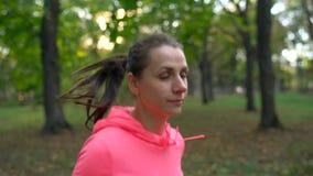 Ciérrese para arriba de la mujer que corre a través de un parque del otoño en la puesta del sol Cámara lenta almacen de video