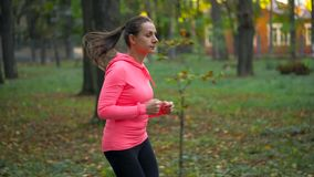 Ciérrese para arriba de la mujer que corre a través de un parque del otoño en la puesta del sol Cámara lenta almacen de metraje de vídeo