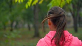 Ciérrese para arriba de la mujer que corre a través de un parque del otoño en la puesta del sol Visión desde la parte posterior metrajes