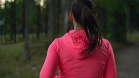 Ciérrese para arriba de la mujer que corre a través de un parque del otoño en la puesta del sol Visión desde la parte posterior almacen de video