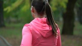Ciérrese para arriba de la mujer que corre a través de un parque del otoño en la puesta del sol, visión trasera metrajes