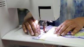 Ciérrese para arriba de la mujer que cose usando la máquina eléctrica almacen de metraje de vídeo