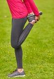 Ciérrese para arriba de la mujer que estira la pierna al aire libre Imagenes de archivo
