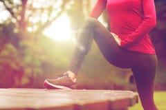 Ciérrese para arriba de la mujer que estira la pierna al aire libre Foto de archivo