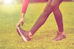 Ciérrese para arriba de la mujer que estira la pierna al aire libre Imágenes de archivo libres de regalías