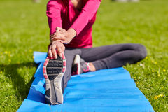 Ciérrese para arriba de la mujer que estira la pierna en la estera al aire libre Fotos de archivo