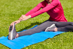 Ciérrese para arriba de la mujer que estira la pierna en la estera al aire libre Fotografía de archivo libre de regalías