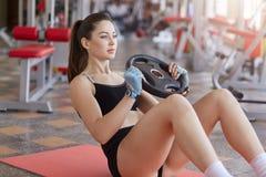 Ci?rrese para arriba de la mujer que hace ejercicios del ABS con la placa del peso mientras que se sienta en la estera del deport foto de archivo
