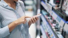 Ciérrese para arriba de la mujer que las manos utilizan el teléfono en tienda cosmética, cámara lenta metrajes